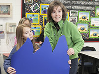 Teacher and student holding ocean waves made of blue cardboard