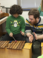Teacher helping a student play the xylophone