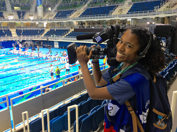 Student holding a TV camera by an Olympic swimming pool