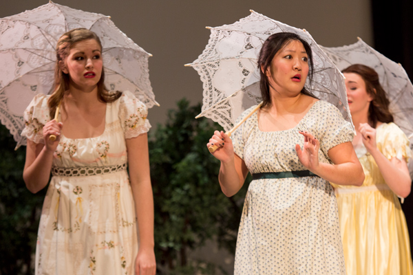 Students in dresses with parasols singing on stage