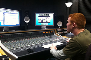 A student at a computer mixing audio tracks
