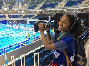 Student holding a camera at an olympic swimming pool