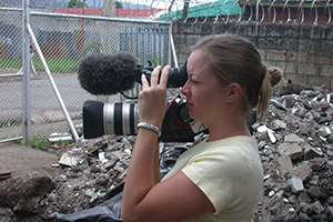 Student filming an outdoor scene with fences and barbed wire