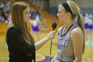 A student sideline reporter interviews a basketball player