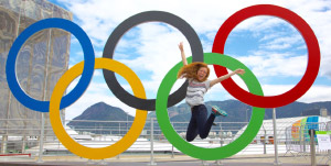 Student jumping in front of Olympic logo