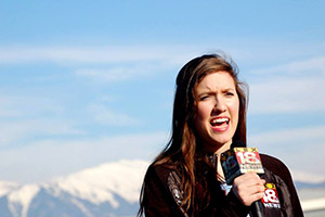 Student reporter with microphone standing with snowcapped mountains in the background