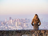 Girl sitting on a ledge with the San Francisco skyline in the background