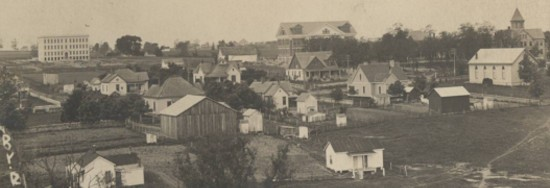 Old photo of a wide-view shot of a hillside with simple houses and buildings