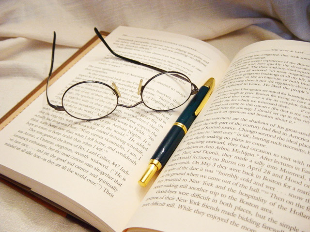 glasses and a pen on an open book