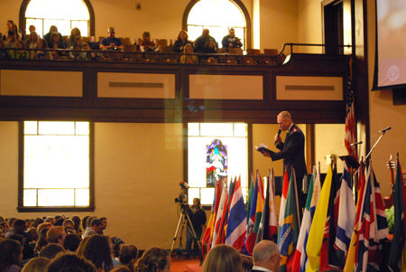 Major Stephen Court opened Monday's Chapel service with scripture as flags representing countries where Asbury students have lived and served lined the platform.