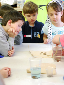 Kindergarteners learn about the effects of acids on metal at Kids College 2013.