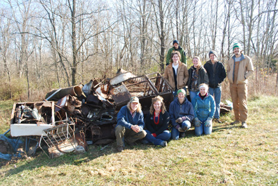 Students in an Adventure Leadership class show one of two piles of material they removed from a local wooded area with hiking trails.