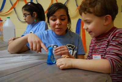 Asbury student Diana Sanchez helped a kindergartener with a chemistry experiment at the 2012 Kids College.