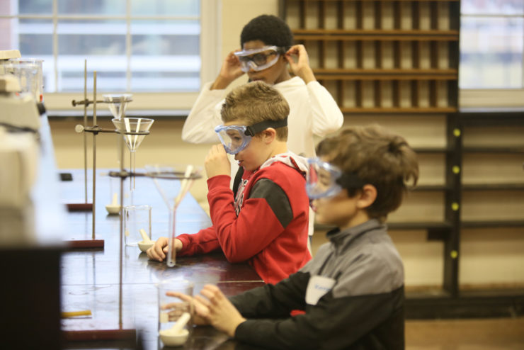 children wearing safety goggles doing chemistry experiments