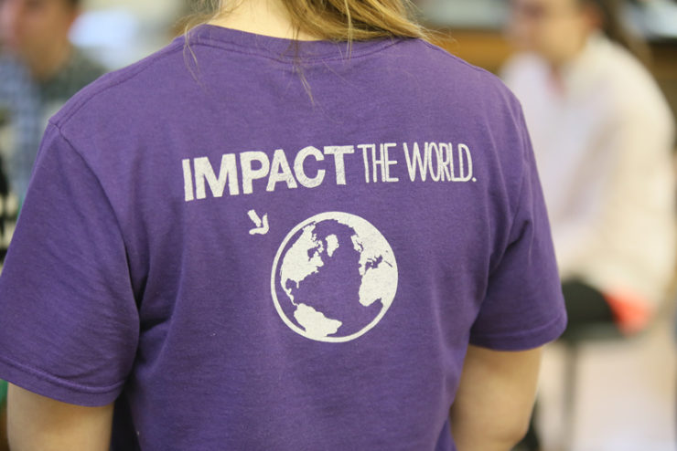 person wearing an Impact the World t-shirt