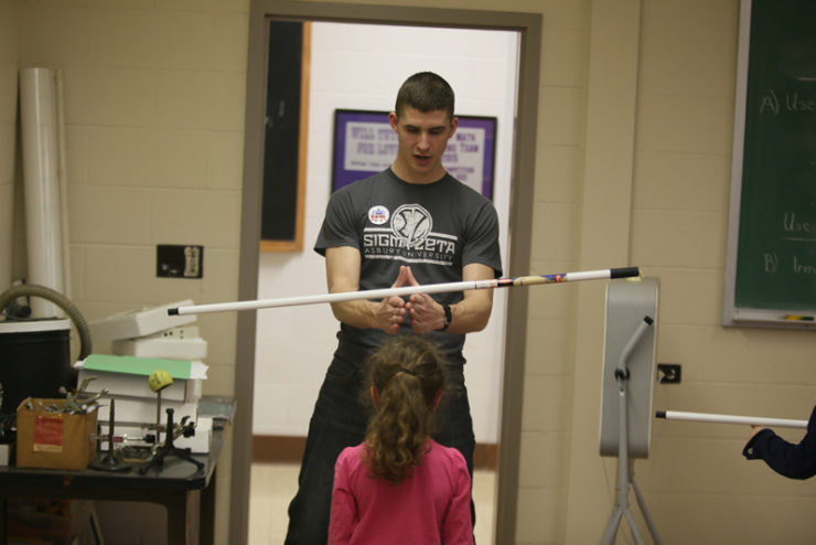 student demonstrating balancing a broomstick