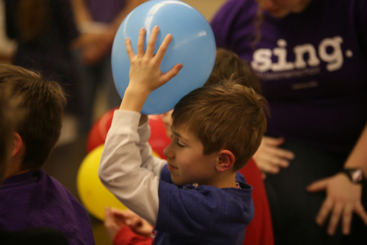 child holding a balloon on his head