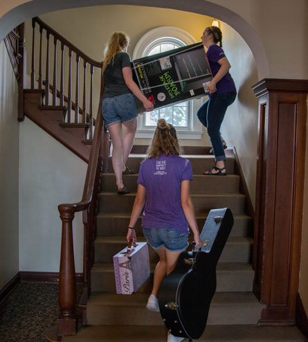 students carrying items up stairs