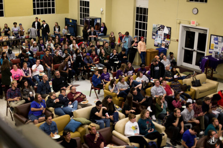 students seated in the student center watching a basketball game