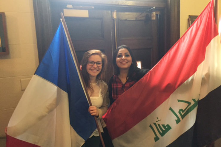 students smiling and holding flags