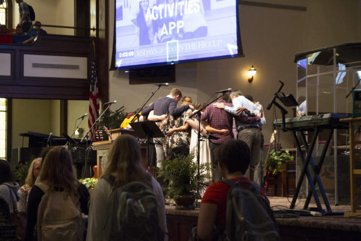 people praying together on stage in chapel