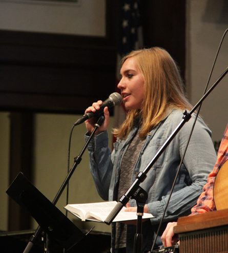 student singing in chapel