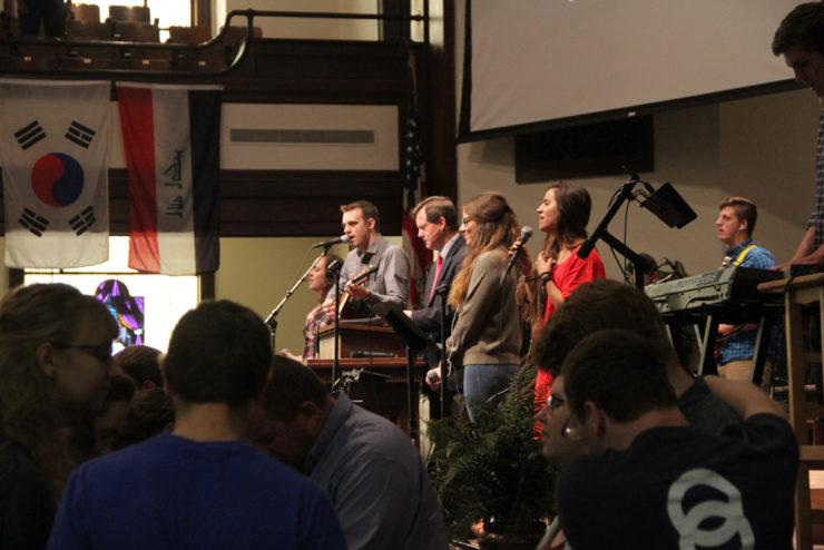 people leading singing in chapel