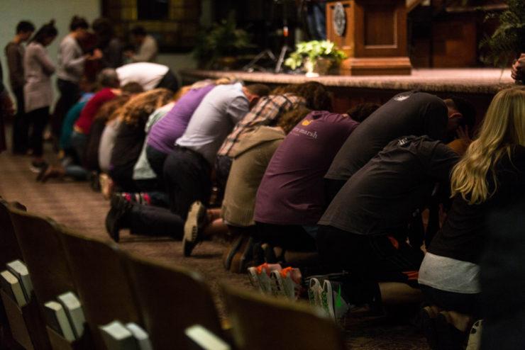 students praying at the altar rail