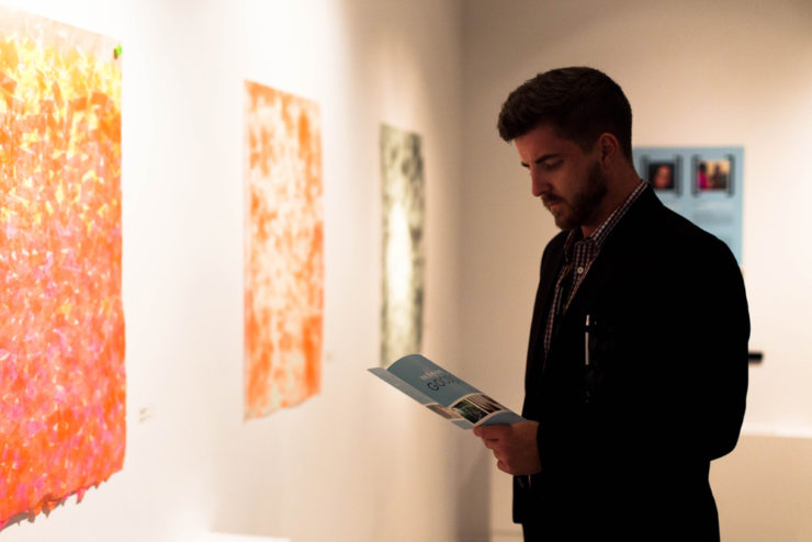 person reading a pamphlet in an art gallery