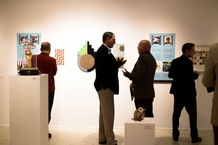 people standing and talking in an art gallery