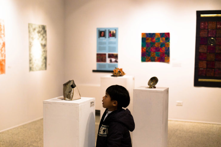 child looking at a ceramic sculpture