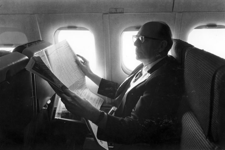 Dr. Dennis Kinlaw reading a newspaper on a plane