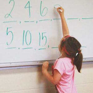 Elementary school student solving math problems at a whiteboard