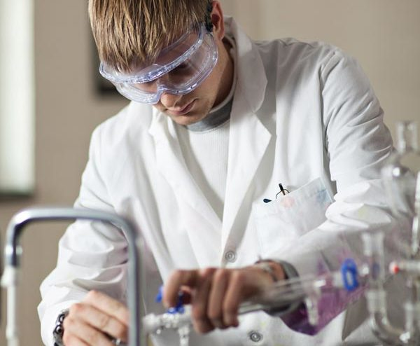 chemistry student pouring a solution into a beaker