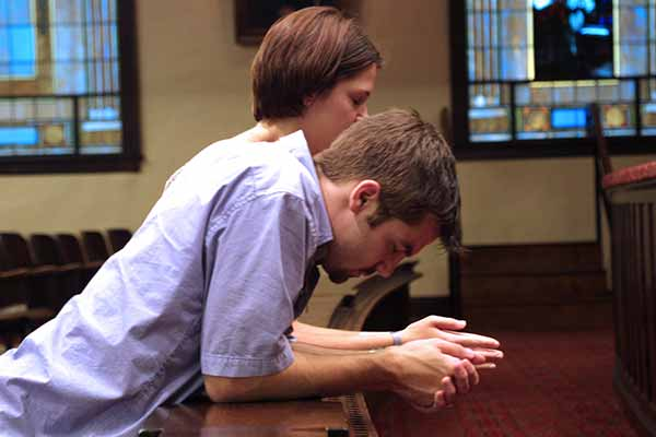 Two students praying at the altar rail in Hughes