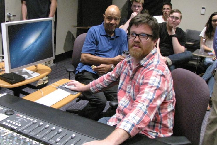 Professors and students collaborating with a musician