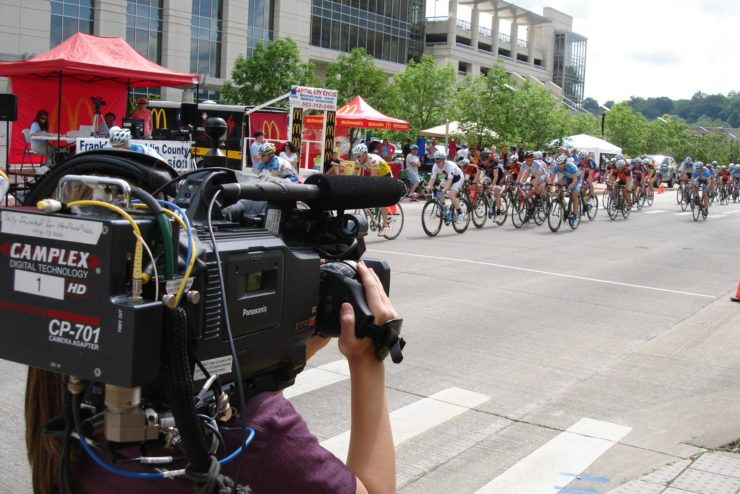 Student holding a TV camera recording a cycling race