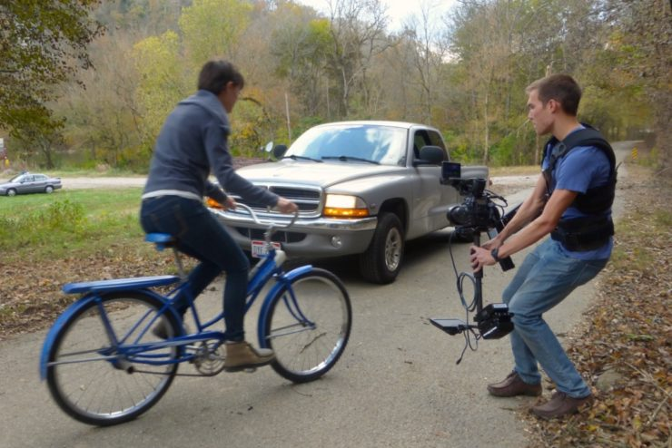Students filming a scene with a bicycle and car