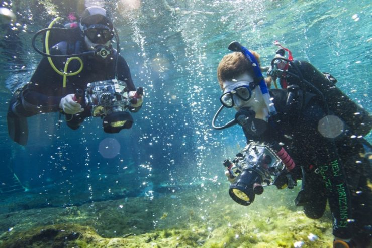 Students in scuba gear filming underwater
