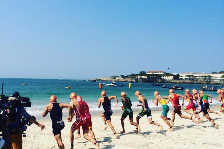 row of Olympic triathletes racing to the ocean