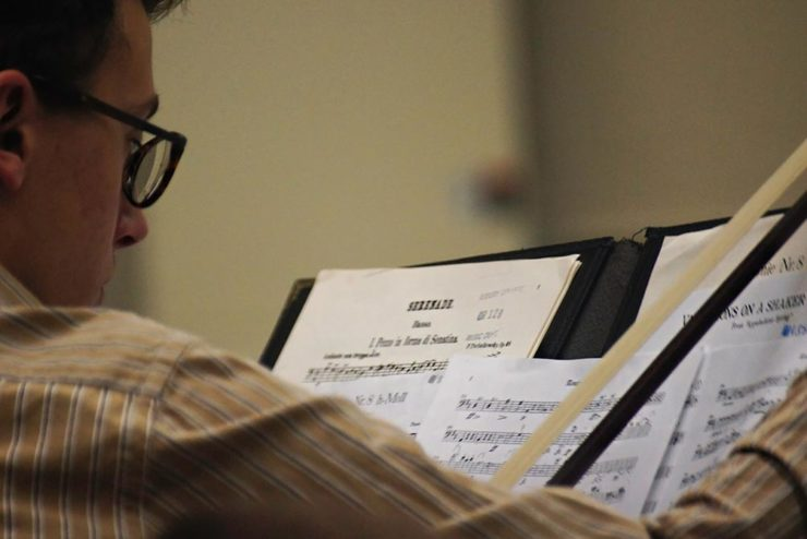 orchestra student looking at sheet music