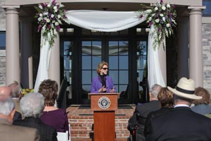 Dr. Gray speaking from a podium in front of a building