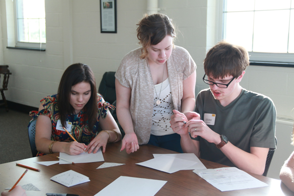 Three students at a table solving math problems