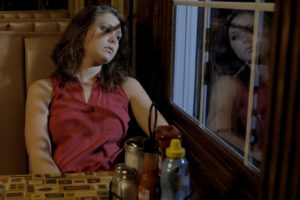 Student actress sitting in a restaurant booth, looking outside