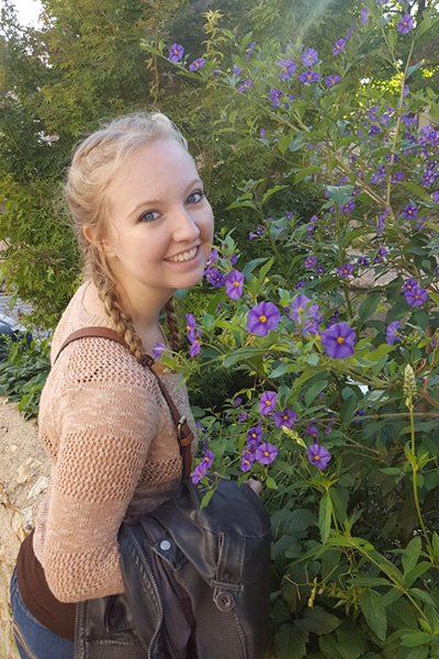 Student posing in front of flowers