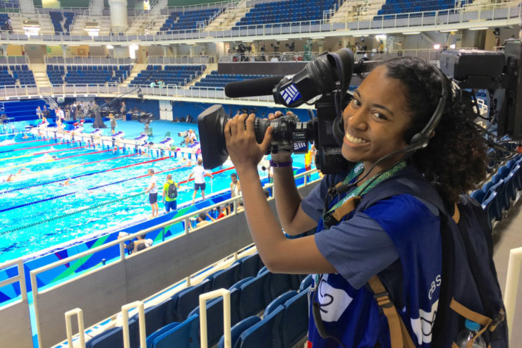 Student holding a TV camera at the Olympics