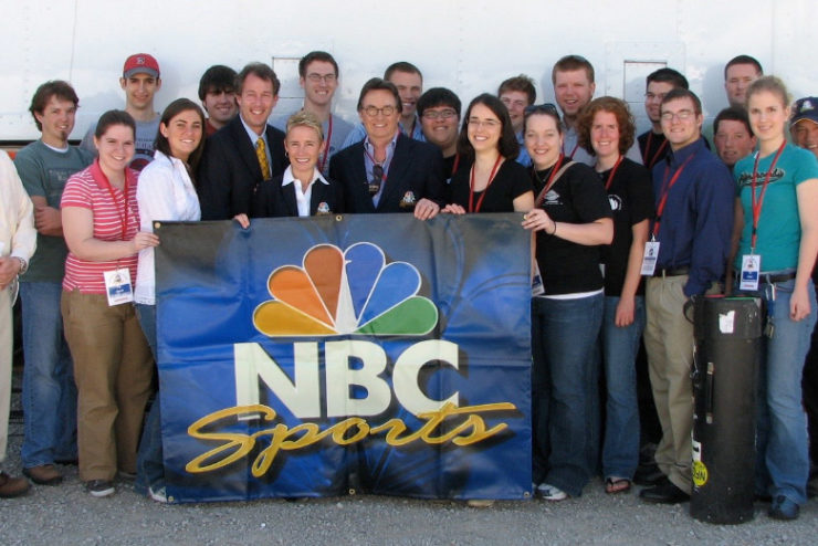 Student interns posing with an NBC Sports banner
