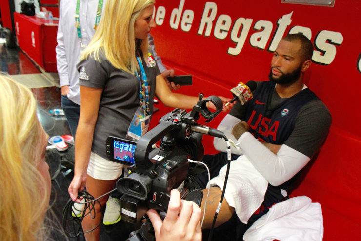 student interviewing a team member of the USA Basketball Team at the Olympics