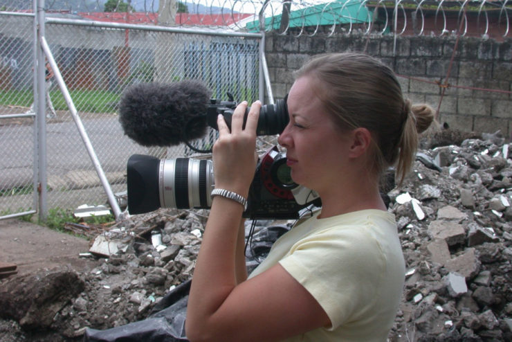 Student with camera filming disaster devastation