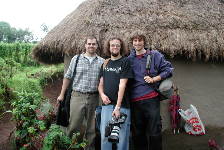 Students posing for a photo in front of a thatched roof hut
